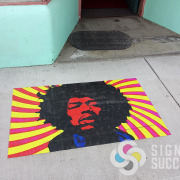 This sidewalk sticker of Jimi Hendrix has been in front of Karenoia store in Hillyard Spokane for a couple of years and still looks great, Signs for Success can do fast work, call now