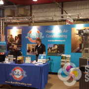 Trade show booth for R&R Heating & Air Conditioning includes the backdrop panels, table throw and promotional products by Signs for Success