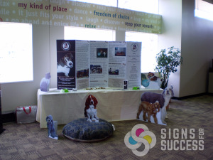 "This kiosk is decorated with full sized animal standee cutouts that are free standing as well as a folding informational ""poster"" standee on the table, foam board printing"