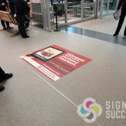 This ad gets walked on thousands of times daily and still looks great, with custom floor decals by Signs for Success at Spokane Airport, ads for Riverpark Square