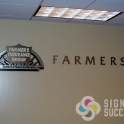 Lobby sign for Farmers Insurance, cut acrylic with metal laminate for lobby wall sign in offices, by Signs for Success