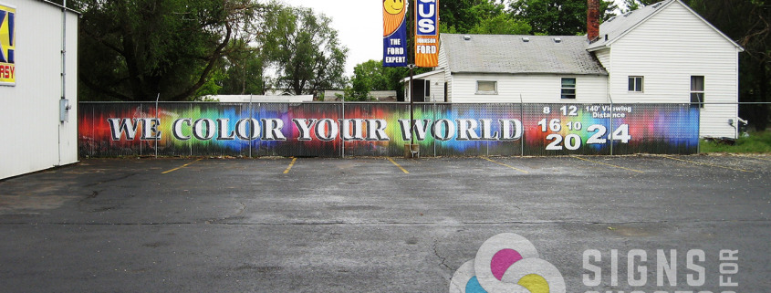 Custom Printed graphics decorate this chain link fence with slats cut down and inserted, by Signs for Success, privacy fencing doesn't have to be boring
