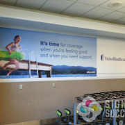 Temporary vinyl that can actually be moved if desired, with this fabric decal wall wrap for United Healthcare ad at Spokane Airport