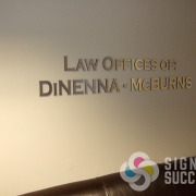 Law offices of: DiNenna-McBurns lobby sign, brushed gold metal laminate on black acrylic makes an impact for a lobby sign in your offices, by Signs for Success Spokane, call for fast service now