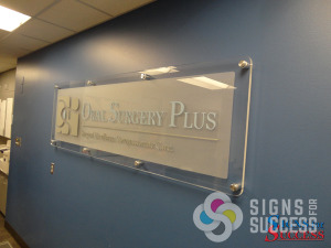 This dimensional lobby sign on clear acrylic looks great mounted with standoffs on the wall, it's a real show piece, by Signs for Success, Spokane for Oral Surgery Plus, office signs, stand-off mounts, lobby signs spokane