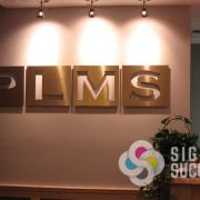 Dimensional letters can be frontlit like these for PLMS in Spokane, Brushed gold aluminum metal laminate on acrylic, mounted with studs for a great looking lobby sign, law office signs