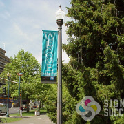 Riverfront Park welcome pole banner on post by signs for Success, with changeable sponsor decals