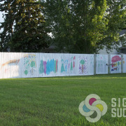 Privacy fencing doesn't have to be boring, see this North Dakota fenceline decorated with Custom chain link fence slats by Signs for Success Spokane
