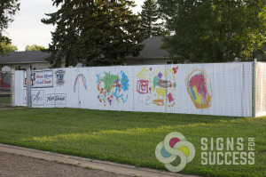 Custom Chain Link Fence Slats, Fence Slat Signs printed with this daycare children's artwork and sponsor logos for a unique advertising that the parents and local businesses love in North Dakota, by Signs for Success