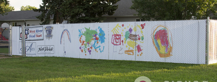 Custom Chain Link Fence Slats printed with this daycare children's artwork and sponsor logos for a unique advertising that the parents and local businesses love in North Dakota, by Signs for Success