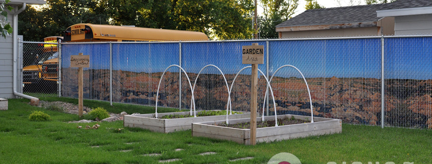The inside of the chain link fence slats show a desert landscape, very beautiful against the grass, gives privacy for this business or home, by Signs for Success