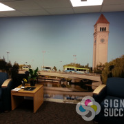 Spokane Transit new office lobby wall wrap with Spokane mural showing Clock Tower and busses, printed and installed by Signs for Success
