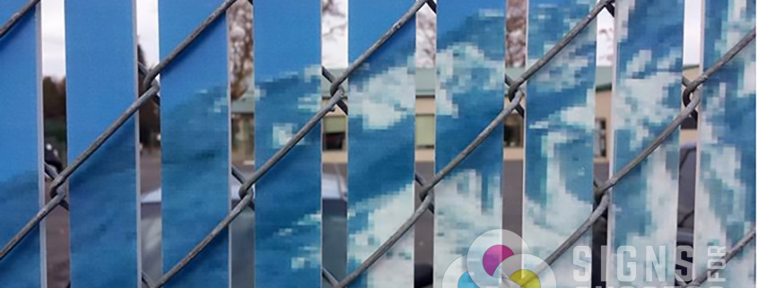 Close up view of spacing on custom printed chain link privacy slats by Signs for Success in Spokane