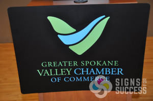 Greater Spokane Valley Chamber needed a podium sign for the unveiling of their new logo design, with White and colored inks on black PVC sintra, this one looks great, custom signs spokane