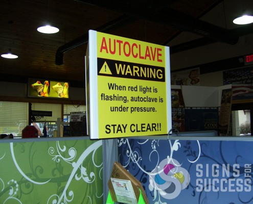 This hanging sign for autoclave is three sided and hangs from the ceiling in manufacturing facility to show warning sign, dimensional hanging signs spokane