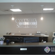 Brushed Aluminum Logo Sign matches custom ADA signs throughout spokane office